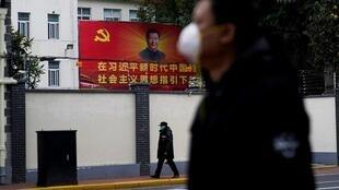 People wearing masks walk past a portrait of Chinese President Xi Jinping in Shanghai.