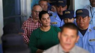 Policiais acompanham a ex-primeira-dama de Honduras Rosa Elena Bonilla de Lobo, detida sob acusação de desvio de dinheiro público.