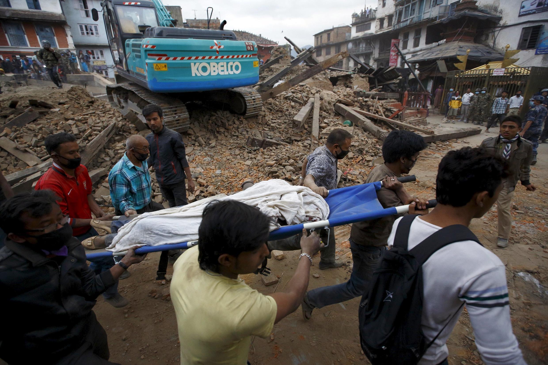 Voluntários ajudam na retirada de corpos dos destroços do violento terremoto que atingiu o Nepal neste sábado (25).