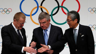International Olympic Commitee President Thomas Bach (C) prepares to shake hands with IOC Vice President John Coates (L) and Japanese Olympic Committee President Tsunekazu Takeda during a photo session at a news conference in Tokyo on 20 November  2013.