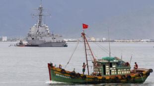 Một tàu đánh cá Việt Nam ở cảng Tiên Sa, Đà Nẵng, đằng xa phía sau là khu trục hạm USS Chung Hoon của Hoa Kỳ trong chuyến thăm Việt Nam ngày 15/07/11.