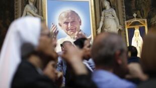 A nun prays near a portrait of Pope John Paul II in a Rome church, 26 April, 2014