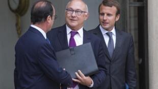 François Hollande con los ministros de Finanzas, Michel Sapin, y de Economía, Emmanuel Macron, este 27 de agosto de 2014.