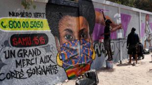 Une fresque peinte sur un mur de la ville de Dakar sensibilise à la lutte contre le coronavirus.