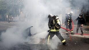 Firefighters try to extinguish a fire during the traditional May Day labour union march with French unions and yellow vests protesters in Paris