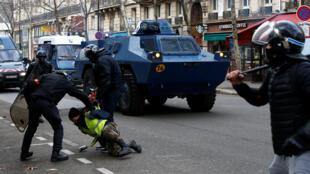 巴黎街头警察正在控制一名黄背心,背后是防暴装甲车。