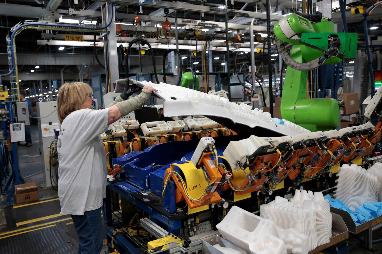 Operário de montagem da General Motors trabalha junto com um robô na construção de veículos Chevrolet Bolt EV e Sonic, em Lake Orion, EUA. 19 de março de 2018.