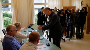 Leif-Erik Holm (C) of the anti-immigrant Alternative for Deutschland (AfD) receives his ballot paper for the Mecklenburg-Vorpommern state election