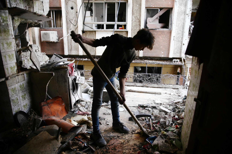 Homem limpa o que sobrou de sua casa na região da Guta Oriental, perto de Damasco