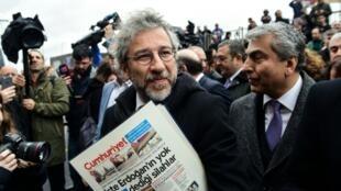 El periodista Can Dundar llega al tribunal con un ejemplar del periódico que dirige, este viernes 25 de marzo en Estambul