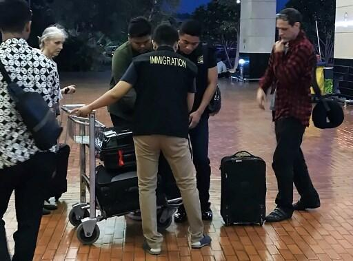 Le Français Michaël Blanc (d) et sa mère Hélène Le Touzey (g) ont été accompagnés à l'aéroport Soekarno-Hatta de Jakarta par des agents de l'immigration, le 21 juillet 2018.