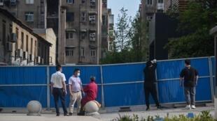 Unos trabajadores instalan unas barreras el 12 de mayo de 2020 cerca del complejo residencial de la ciudad china de Wuhan donde se detectaron cinco nuevos casos de coronavirus