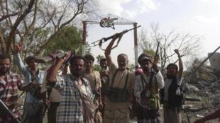 Wapiganaji wanaounga mkono serikali nchini Yemen wakiwa mbele ya kambi ya jeshi ya al-Anad, Agosti 3, 2015.