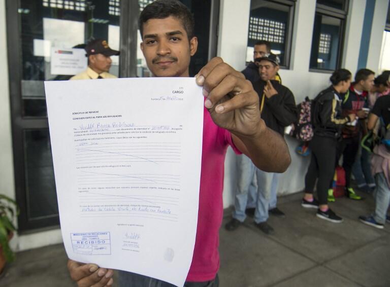 En Tumbes, Perú, un migrante venezolano muestra su solicitud de asilo.