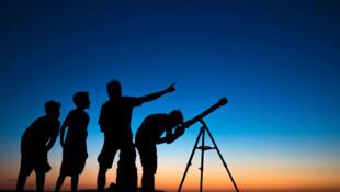 Des gens scrutent le ciel à l'aide d'un télescope.