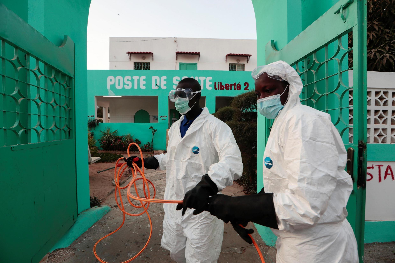 Des agents d'hygiène locaux se préparent à désinfecter un centre de santé pour arrêter la propagation du coronavirus. Dakar (Sénégal), le 1er avril 2020.