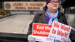 Funcionário da Receita Federal dos EUA (IRS) manifesta com cartazes em frente ao prédio do governo federal contra a paralisação do governo dos EUA, em Ogden, Utah. 10/01/19.
