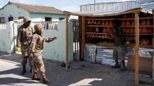 Un soldat demande à un vendeur de fermer sa boutique alors que les autorités tentent de faire respecter le confinement de 21 jours visant à limiter la propagation du Covid-19, dans le canton de Khayelitsha près de Cape Town, le 27 mars 2020.