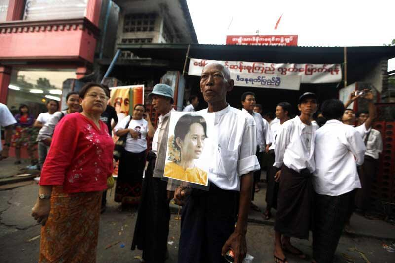 Activists hold portaits of Myanmar's detained pro-democracy leader Suu Kyi as they wait for the news of her possible release in Yangon