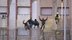 Inmigrantes africanos escalan la reja que marca la frontera entre el norte de Marruecos y el énclave español de Melilla, 28 de febrero de 2014