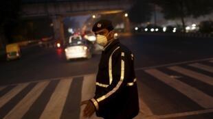 Un policier au milieu de la circulation de New Delhi porte un masque pour se protéger de la pollution.