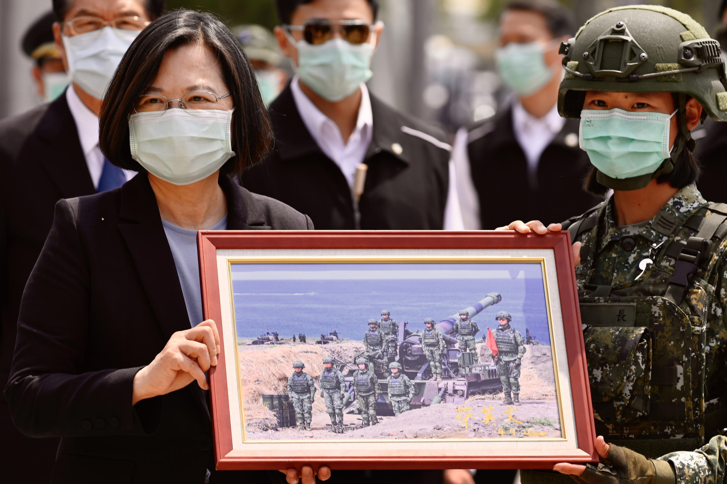Taiwan President Tsai Ing-wen receives a framed photograph from a masked soldier amid the COVID-19 coronavirus pandemic during a visit to a military base in Tainan on April 9, 2020