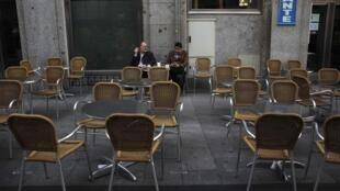 Dos hombres discuten en una terraza de Madrid sobre la crisis y las elecciones.