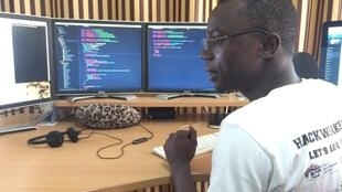 Hassan Jallow reviews code at the Assutech offices in Brufut Gardens.