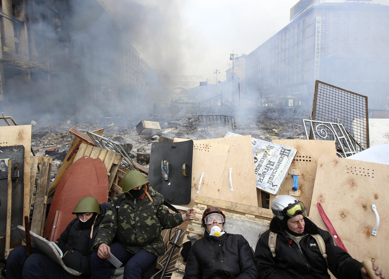 Manifestantes contra o governo ucraniano se protegem em barricada contra forças de segurança.