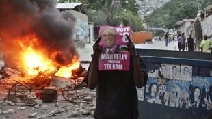 A Haitian holds up a poster of presidential candidate Michel Martelly next to a burning barricade in Port-au-Prince