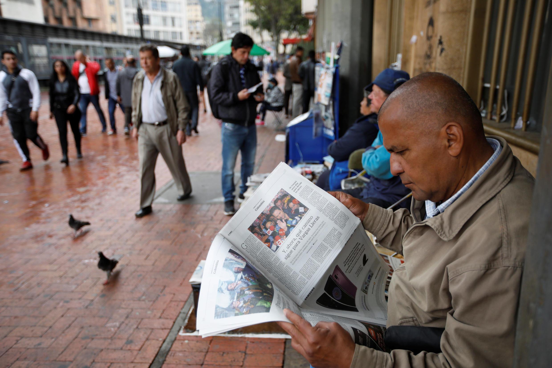 En el centro de Bogotá, un hombre lee una página de periódico con los dos candidatos a la segunda vuelta: Iván Duque y Gustavo Petro.
