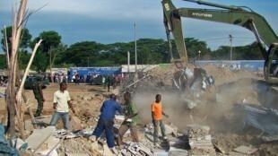 Une pelleteuse s'active dans les décombres de l'immeuble, à Nyagatare, le 15 mai 2013.
