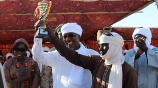 Le président tchadien, Idriss Deby remet le prix à Bicholo Djomboye Bilo, le jockey qui a remporté la course de dromadaires au festival international des cultures sahariennes à Amdjarass, le 1er avril 2019.