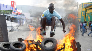 A protester jumps over a burning barricade during a protest against the government in the streets of Port-au-Prince, Haiti