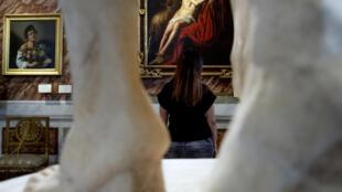 Una visitante contempla el cuadro 'Juan el Bautista', obra del maestro barroco italiano Caravaggio, el 19 de mayo de 2020 en la Galleria Borghese, en Roma