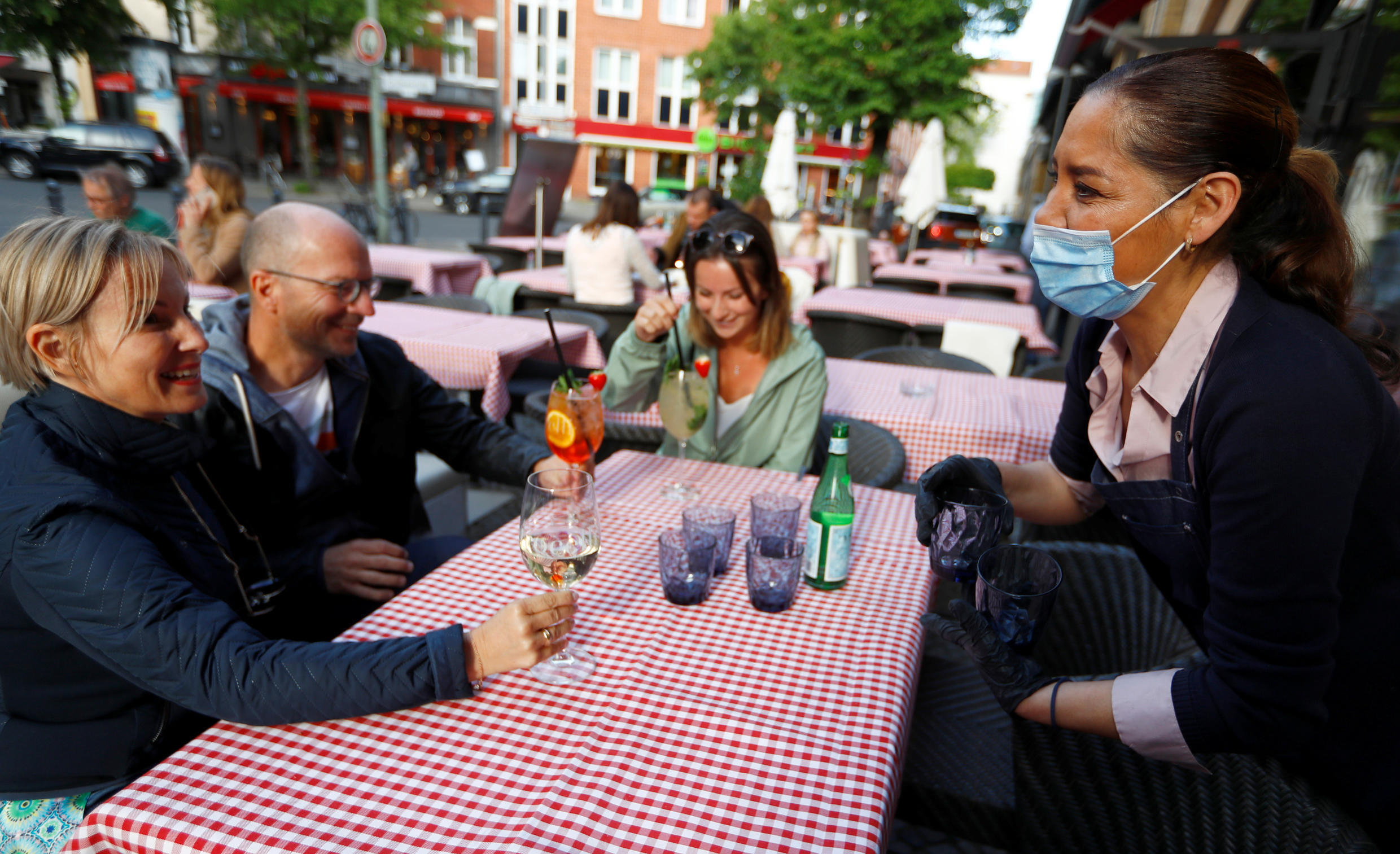 A waitress wearing a protective face mask talks to customers at Petrocelli's Bar, during the coronavirus disease (COVID-19) outbreak, in Berlin, Germany May 16, 2020.