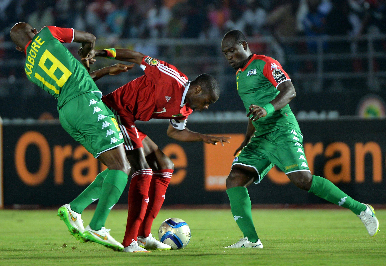 Burkina Faso's Charles Kabore (L) and Djakaridja Kone (R) challenge Congo's Prince Oniangue