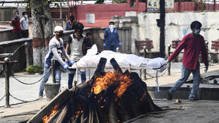 Relatives push a stretcher with the body of a person who died from the coronavirus, before the cremation in a pyre at the Nigambodh Ghat in New Delhi