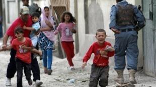Des enfants fuient le lieu des combats déclenchés par une attaque revendiquée par les talibans afghans, à Kaboul, ce vendredi 24 mai.
