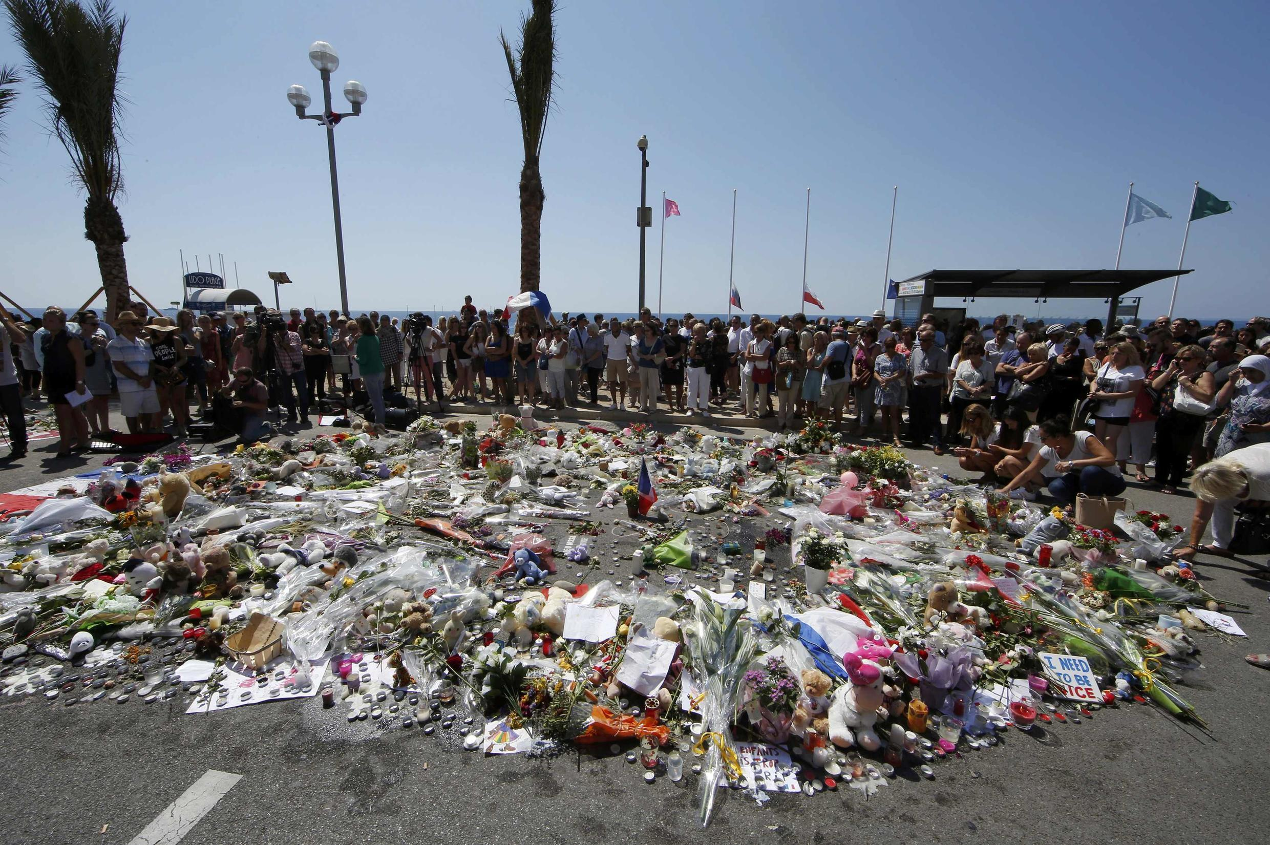 People gather around a makeshift memorial with flowers and candles placed along the Promenade des Anglais to pay tribute to the victims of the Bastille Day attack in Nice.
