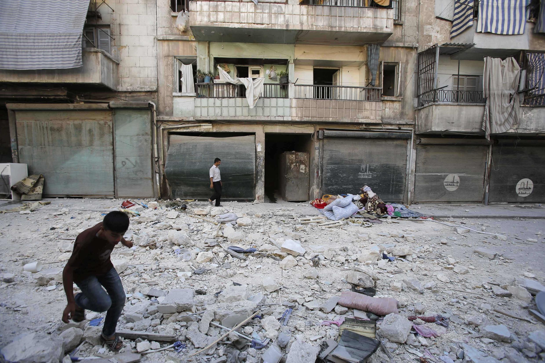 Civis diante do prédio onde moravam, atingido por bombardeios realizados pelas forças do governo de Bashar al-Assad neste sábado..