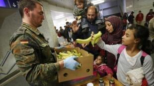 Distribution de nourriture aux migrants à leur arrivée, à la station ferroviaire Schoenefeld avant leur transfert vers un camp de réfugiés. Berlin, le 5 octobre 2015.