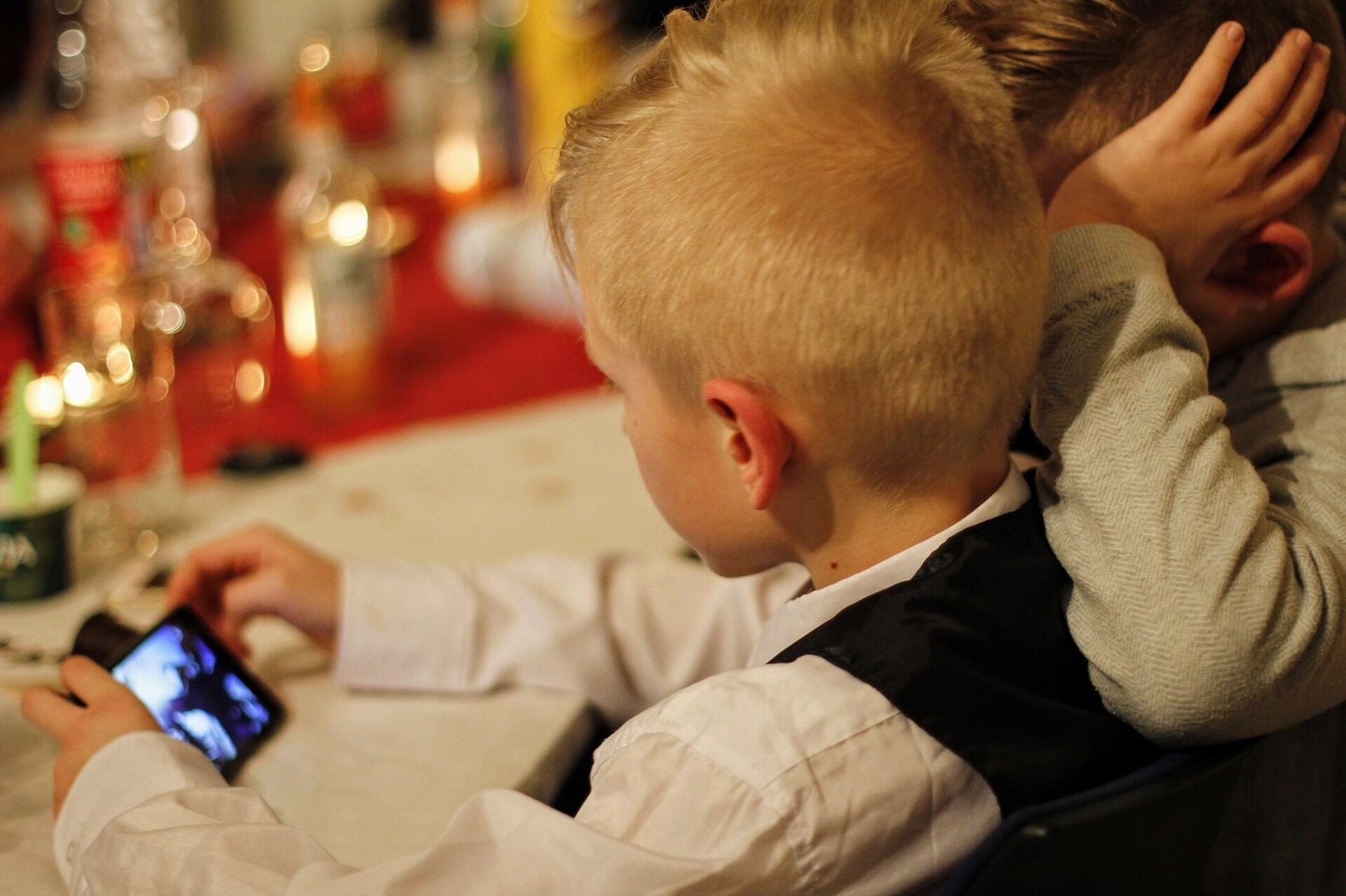 Enfants jouant avec un smartphone.