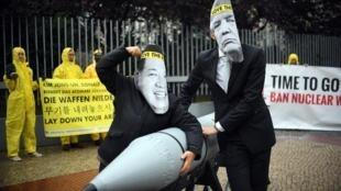 Militantes do ICAN com máscaras de Donald Trump e de Kim Jong-Un diante da embaixada norte-coreana em Berlim, no passado 13 de Setembro.