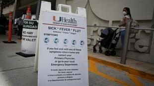 Un panneau placé devant l'hôpital Jackson Memorial dans le Conté de Miami-Dade en Floride recommande aux personnes souffrant de symtômes de la fievre de retourner chez eux et de contacter leur médecin traitant, le 18 juin 2020.