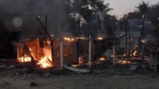 A house burns in a Thai village near the border between Thailand and Cambodia