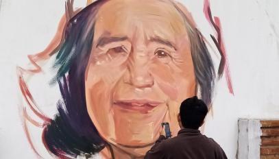 Daniel Manrique pinta o retrato de Eustacia, vítima da Covid-19, em um muro do bairro de Leticia, em Lima.