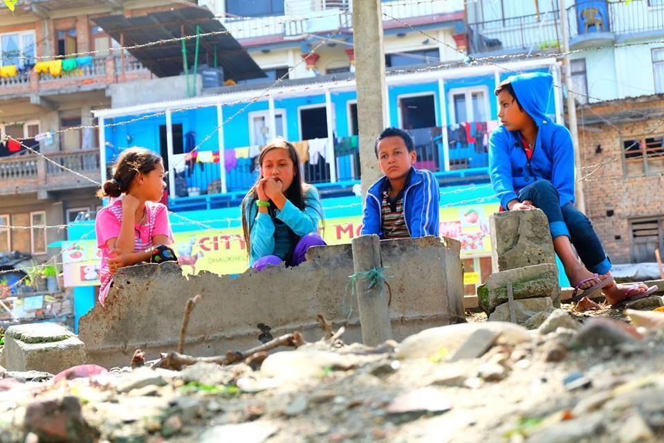 Dans Katmandou, la capitale népalaise dévastée par le séisme du 25 avril, des enfants autour d'un puit.