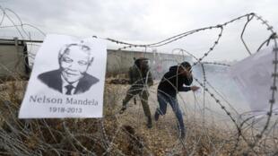 Un portrait de Nelson Mandela sur des fils barbelés lors d'une action contre la colonisation israélienne, près de Ramallah, le 6 décembre 2013.