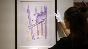 """A worker holds a sketch by Nelson Mandela -- """"The Cell Door, Robben Island"""" -- on April 26, 2019 in New York City"""